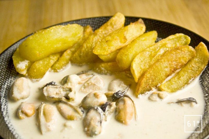 Plat de moules au Munster et vin jaune accompagnées de pommes Pont Neuf dans une assiettes noire