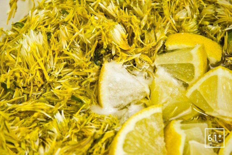 Ajouter l'acide citrique et le citron au mélange d'eau et de fleurs de pissenlit