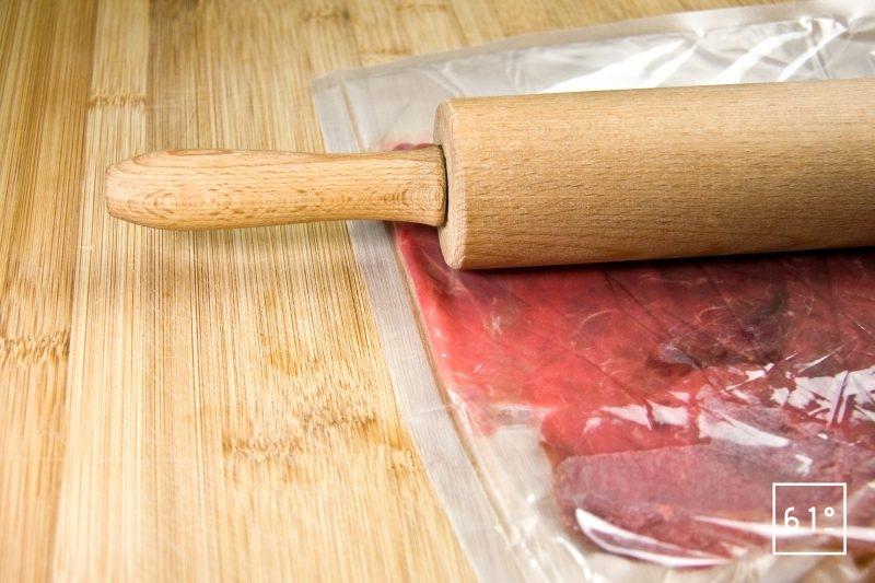 Aplatir la viande de bœuf avec un rouleau à pâtisserie pour former un carpaccio extra fin