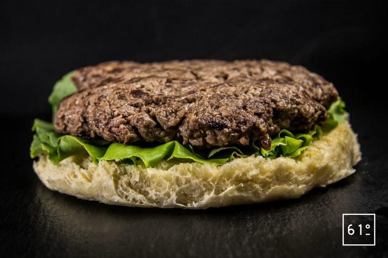 Déposer le steak de viande maturée cuit sous vide sur la salade romaine - burger à la salade César