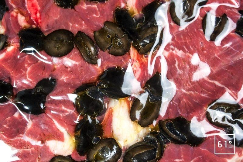Mettre l'entrecôte, les olives noires, et l'huile d'olive fruité noir sous vide