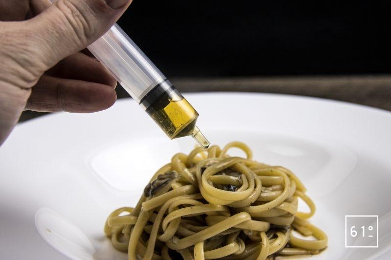 Linguine aux huîtres et bouillon de calmars grillés accompagnées de cognac et caviar - ajouter le cognac et l'huile d'olive