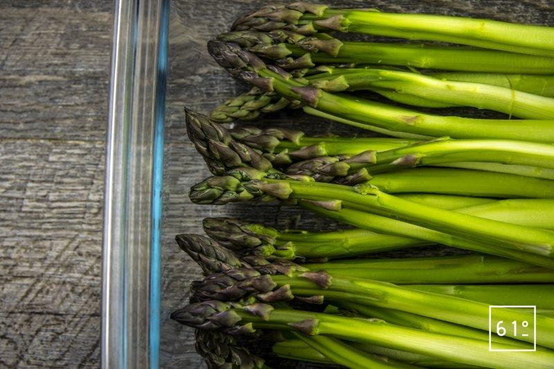 Asperges vertes rôties au four accompagnées d'un mélange d'huile d'olive et de vinaigre dashi - ranger les asperges dans un plat et arroser d'huile d'olive