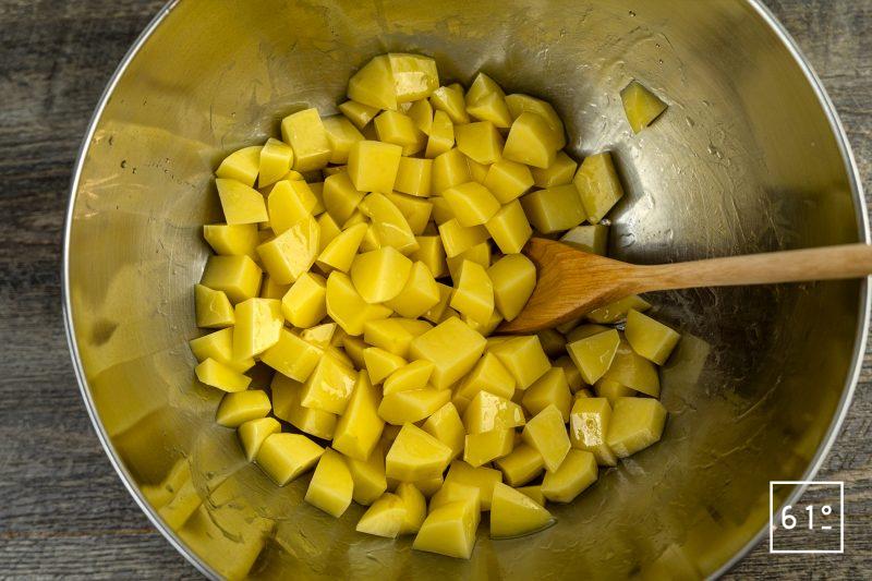 Batata harra - mélanger les morceaux de pomme de terre et l'huile